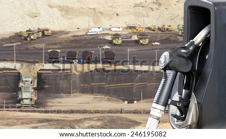 Fuel dispenser with coal as a background in the concept of power. - stock photo