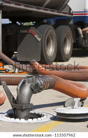 Fuel drop hose transferring gasoline into filling station gas reservoir