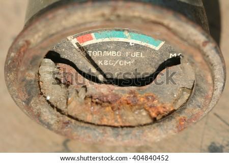 Fuel gauge close up on the brown background. Old, broken, vintage fuel gauge. - stock photo