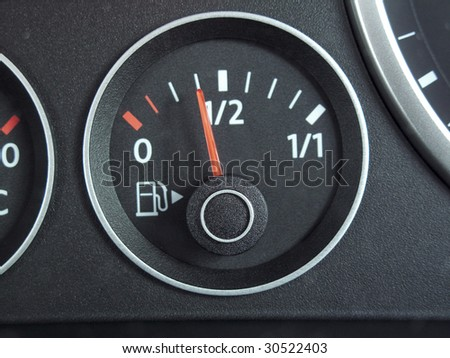 fuel gauge from a car dashboard with needle on 1/2 full