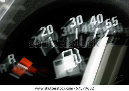 Fuel gauge of a car in dynamic motion blurr - stock photo