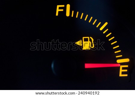 Fuel gauge showing empty tank. Yellow glowing and lit meter with red needle. Isolated against a black background. - stock photo