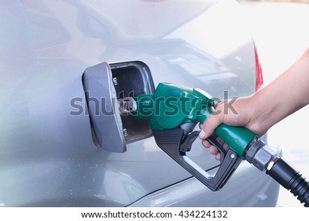 Fuel nozzle add fuel in car at gas station,Thailand - stock photo