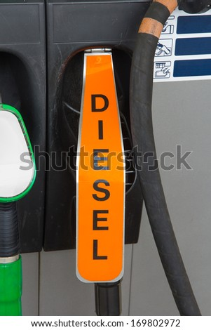 Fuel nozzle behind orange flap indicating diesel at gas station - stock photo