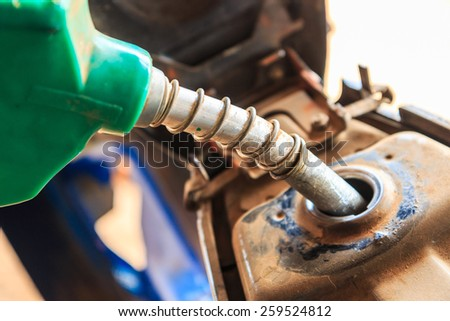 fuel nozzle in pouring to motorcycle old - stock photo