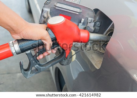 Fuel nozzle to release fuel into car at gas station and control by hand