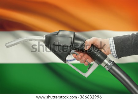 Fuel pump nozzle in hand with flag on background - India - stock photo