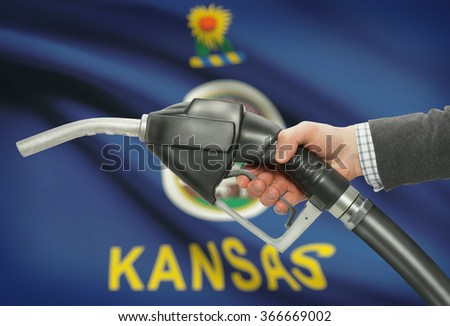 Fuel pump nozzle in hand with US states flags on background - Kansas - stock photo