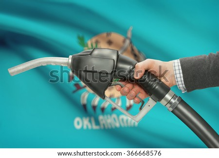 Fuel pump nozzle in hand with US states flags on background - Oklahoma - stock photo