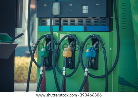 Fuel pumps at a petrol gas station , process in vintage style