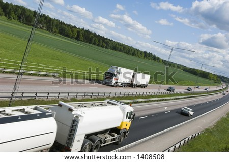 fuel-truck speeding on busy highway in country-side - stock photo