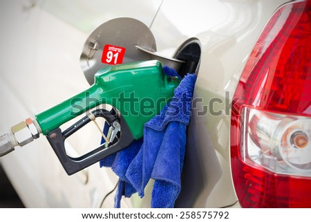 Fueling nozzle inserted into petrol tank at gas station for gasoline filling with cleaning cloth. - stock photo