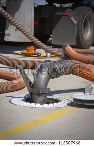 Fueling truck with drop hose connected to underground fuel tank