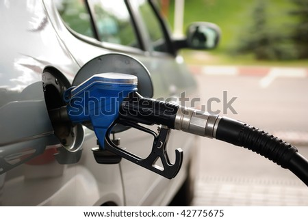 fuelling nozzle inserted into petrol tank at gas station for gasoline filling - stock photo