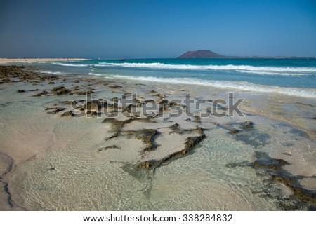 Fuerteventura, Canary Islands, Corralejo Flag Beach, low tide shows volcanic rocks at the bottom - stock photo