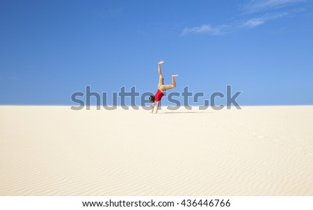 Fuerteventura sand dunes in the north of the island, teenage boy in red t-shirt trying handstands