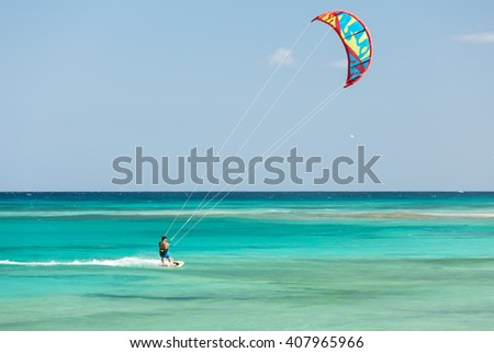 FUERTEVENTURA, SPAIN - SEPTEMBER 15, 2015: Unknown kitesurfer surfing on a flat azure water of Atlantic ocean in Corralejo, Fuerteventura, Canary islands, Spain - stock photo