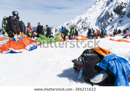 Fuessen, Germany - April 9, 2015: paraglider pilots in a row waiting with their umbrellas on the snow-covered preparation station on the Tegelberg near Fuessen City