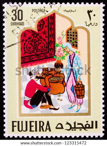 FUJAIRAH - CIRCA 1967: A stamp printed in Fujairah shows the images of man and woman with gold from the story of Ali Baba, circa 1967.