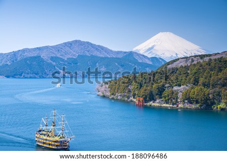 FUJI MOUNTAIN, JAPAN-APRIL 5, View to Fuji Mountain and Ashi Lake at Hakone region on April 5, 2014. Pirate ship does round trip over lake. Ship is very popular attraction for local tourist.  - stock photo