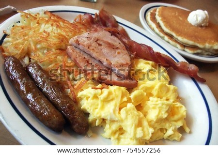 Full American Breakfast with sausage, ham, scambled egg, pancake and hash brown, served on oval china plate
