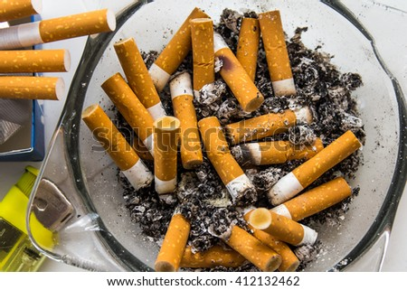 Full ashtray with smoked cigarettes and lot of ashes on white table. Lighter and the cigarettes near it - stock photo