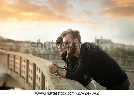 Full beard man with beautiful woman have fun in the city. Stylish couple enjoying beautiful sunset in the city from the the bridge. Blurred background with Prague castle. Color toned image. - stock photo