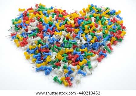 Full big heart shape of colorful push pins isolated on white background.