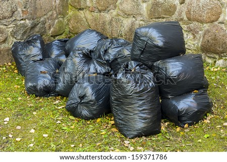 Full black plastic bag in park in the background of stone wall. - stock photo