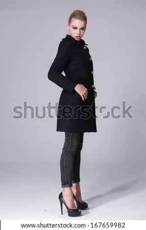 Full body A young pretty standing in a black coat for gray background - stock photo