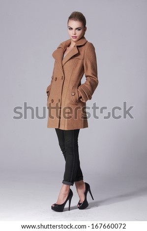 Full body A young pretty standing in coat for gray background - stock photo