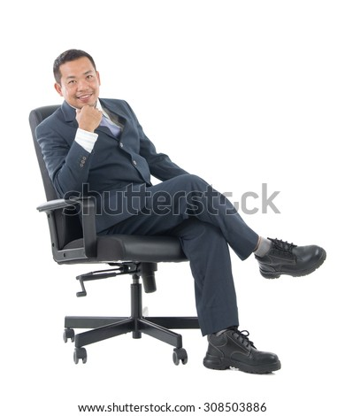 Full body Asian business man seated on chair, arms crossed isolated on white background.