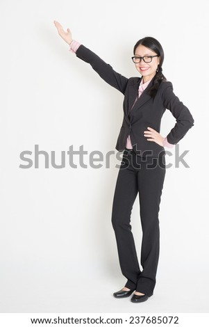 Full body Asian business woman showing copy space, standing on plain background. - stock photo