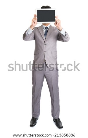 Full body Asian businessman hand holding digital computer tablet covering his face, standing isolated on white background. - stock photo