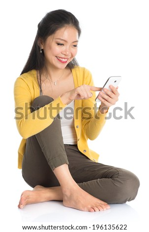 Full body Asian girl in yellow blouse texting with smartphone, seated on floor isolated on white background.