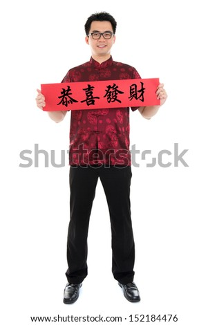 Full body Asian man with Chinese traditional cheongsam or tang suit holding couplet, the Chinese word means congratulations and best wishes for a prosperous New Year.  Isolated on white background. - stock photo