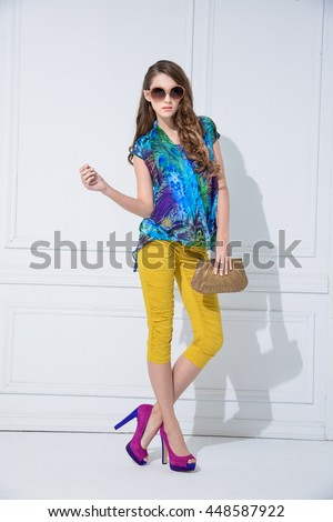 Full body Beautiful female fashion model holding purse posing