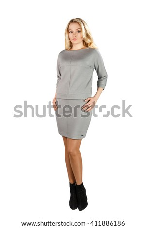 Full body blonde woman in gray dress standing in studio, isolated on white