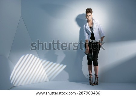 Full body fashion model wearing modern clothing posing in light background - stock photo