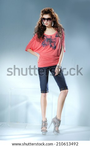 Full body fashion model wearing modern sunglasses posing in light background - stock photo