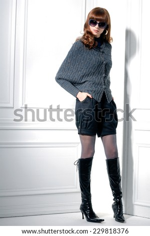 Full body fashion shot of girl in boots with sunglasses posing  - stock photo