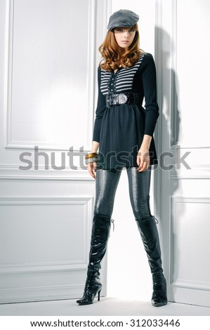 Full body fashion shot of girl with hat posing in studio - stock photo
