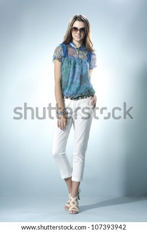 Full body fashion shot of girl with sunglasses posing in light background - stock photo