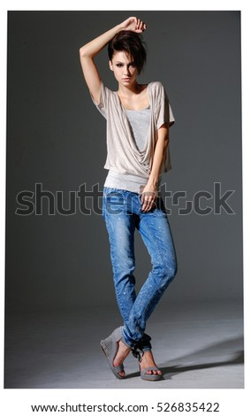 Full body fashion studio portrait of young woman in jeans -gray background