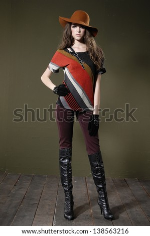 full body fashion woman in hat posing wooden floor on dark background