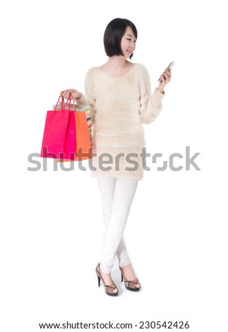 Full body happy shopping woman holding her cell phone posing in studio - stock photo