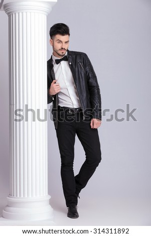 Full body image of a handsome business man pulling his leather jacket while leaning on a white column. - stock photo