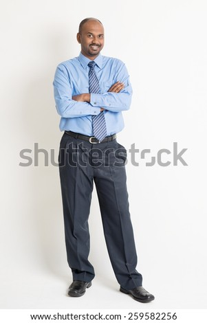 Full body Indian businessman arms crossed standing on plain background with shadow  - stock photo