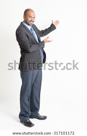 Full body mature Indian business man showing something at blank space, standing on plain background. - stock photo