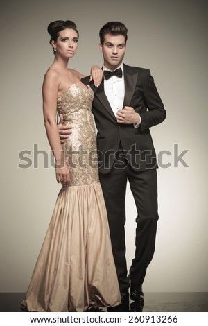 Full body of a elegant couple standing embraced while looking up. - stock photo